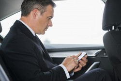 Sending an urgent message. Side view of confident mature businessman typing message on his smart phone while sitting on the back seat of a car